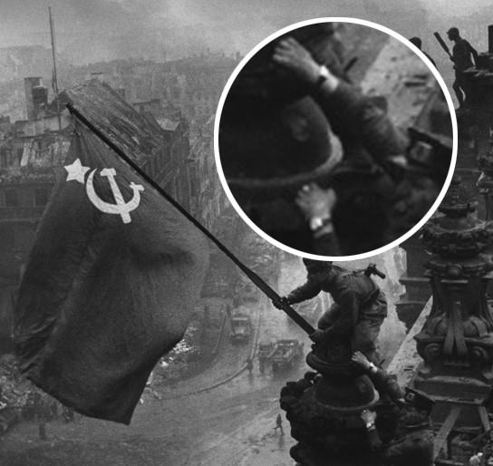 """Zdjęcie - symbol - żołnierze zwycięskiej armii czerwonej wieszają flagę na dachu Reichstagu - gdy przyjrzymy się, jeden z triumfujących  żołnierzy ma na ręku """"łupy wojenne"""", oczywiście nam pokazywano zdjęcia bez tych zgrabionych ozdób."""